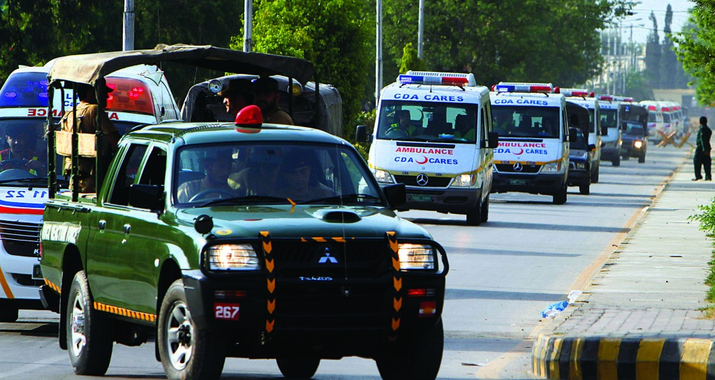A Pakistan's army vehicle leads the way for ambulances carrying caskets of a foreign tourists, who were killed by Islamic terrorists, from a military base to the hospital in Rawalpindi, Pakistan, Sunday. (AP Photo/Anjum Naveed)