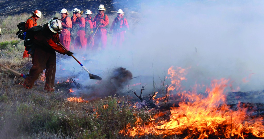 A Los Angeles County hand crew works to contain a flare up alongside a road in Lake Hughes, Calif., early Sunday. (AP Photo/Reed Saxon)