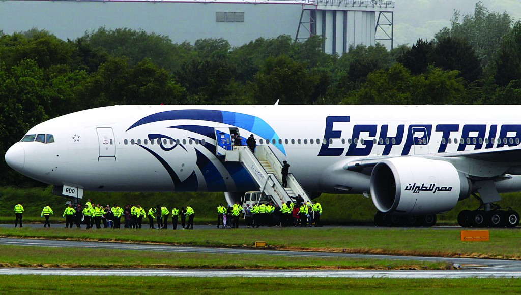 Passengers leave the Egyptair aircraft at Prestwick Airport, Scotland, after it was diverted while en route from Cairo to New York, Saturday. (AP Photo/ Andrew Milligan /PA)