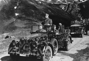 Italy's Prime Minister Benito Mussolini, standing in a camouflaged car, visits the alpine front where Italian troops fought with France. (AP Photo)