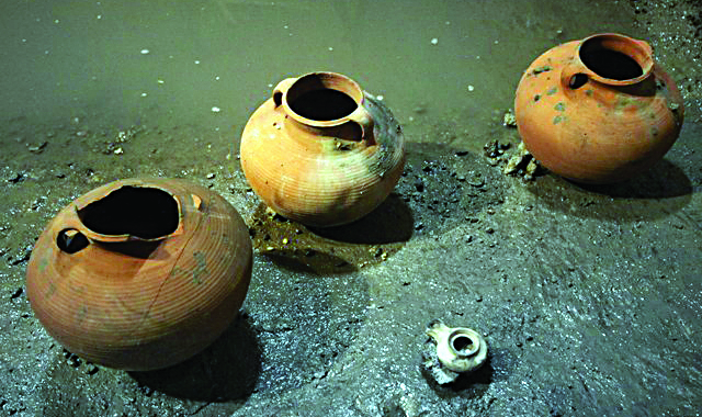 Cooking pots and an oil lamp uncovered in a small cistern in a drainage channel in the Shiloah Pool in Yerushalayim's Old City on Thursday. (Yonatan Sindel / Flash90)