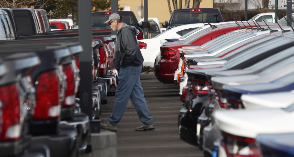 A buyer moves between rows of 2013 Ram pickup trucks and Dart sedans at a Dodge dealership in Littleton, Colo. (AP Photo/David Zalubowski, File)