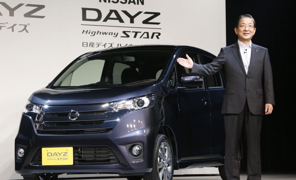 Nissan Motor Co. chief operating officer Toshiyuki Shiga poses in front of its Dayz compact car during a press conference in Tokyo. (AP Photo/Koji Sasahara)