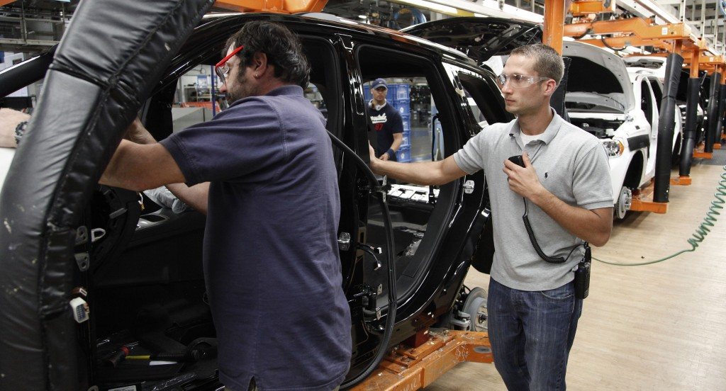 Jeff Caldwell, 29, right, a chassis assembly line supervisor, watches an assembly at the Chrysler Jefferson North Assembly plant in Detroit. The auto industry is on a hiring spree, as car makers and parts suppliers race to find engineers, technicians and factory workers to build the next generation of vehicles. (AP Photo/Paul Sancya)