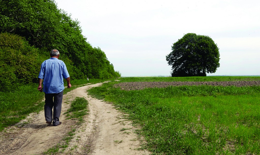 In this picture taken May 10, 2013, Ivan Hrushka, 69, approaches the site of a peasant house (behind tree) where 21 people, including nine children, were burned alive on Dec.3, 1943, in his home village of Pidhaitsi, close to Ukraine's western city of Lutsk. Evidence uncovered by the AP indicates that Ukrainian Self Defense Legion commander Michael Karkoc's unit was in the area at the time of the massacre. (AP Photo/Efrem Lukatsky)