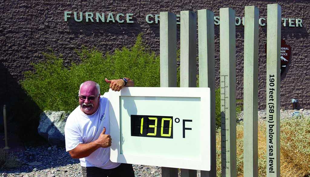 Craig Blanchard, a Park Service employee, poses in front of an unofficial temperature gauge at the Furnace Creek Visitor Center in Death Valley National Park. (REUTERS/Steve Marcus)