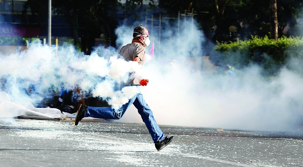 A demonstrator throws a tear gas canister back at riot police during a protest against Turkey's Prime Minister Tayyip Erdogan and his ruling AK Party in central Ankara. (REUTERS/Umit Bektas)