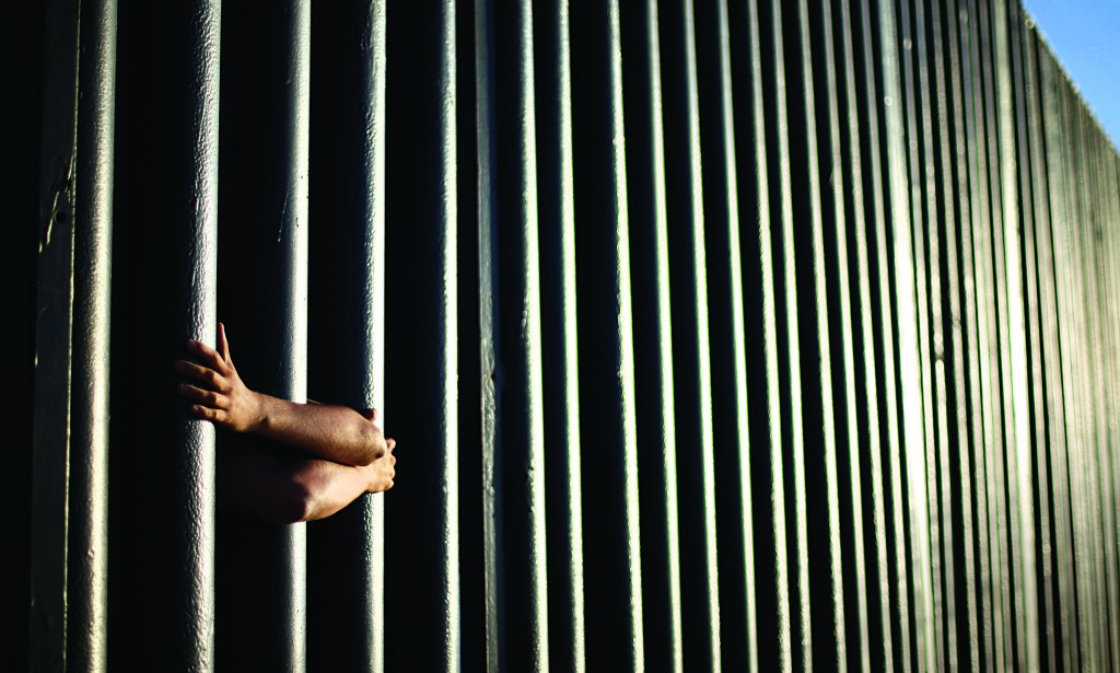 Hands from Daniel Zambrano of Tijuana, Mexico, hold on to the bars that make up the border wall separating the U.S. and Mexico as the border meets the Pacific Ocean in San Diego Thursday. (AP Photo/Gregory Bull)