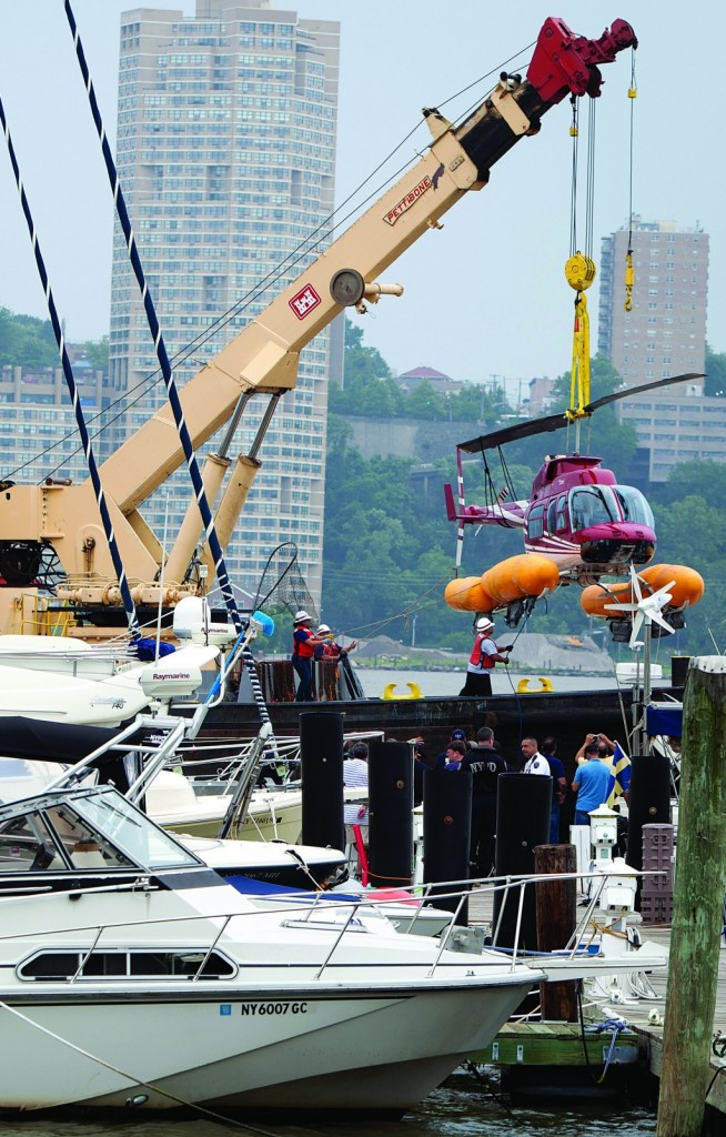 The downed helicopter is hoisted onto an Army Corp of Engineers vessel after an emergency landing on the Hudson River, Sunday. (AP Photo/Carlo Allegri)