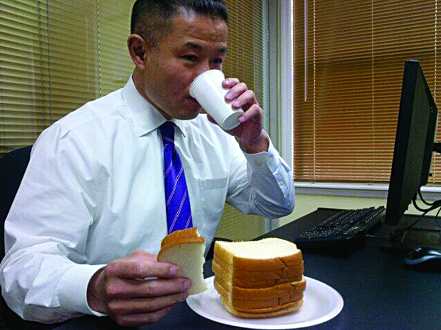 """City Comptroller John Liu, a New York mayoral candidate, eating lunch Tuesday morning — what he called """"white bread on white, with a cup of NYC tap"""" — after he accepted the Food Stamp Challenge in which he will subsist solely on a diet allowable by the federal poverty program."""