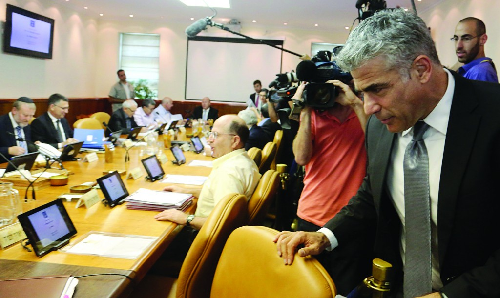 Israel's Finance Minister Yair Lapid takes his seat at the weekly Cabinet meeting on Sunday, the day VAT reached 18 percent for the third time in the state's history. (Israel Sellem/POOL/FLASH90)