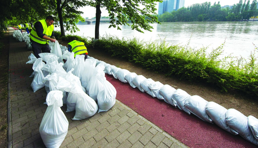 Workers prepare sandbags on the pavement in front of a hotel on Margaret Island on the River Danube in Budapest, Hungary, Wednesday, as flood prevention efforts continue. The river level is expected to peak next Monday. Heavy rainfall and swollen rivers have already caused flooding in parts of Germany, Austria and the Czech Republic. In Germany, desperate families have been plucked from rooftops by helicopters, cars have been swept away by raging torrents and levees failed without warning Wednesday as central Europe was inundated. (AP Photo/MTI, Tibor Illyes)