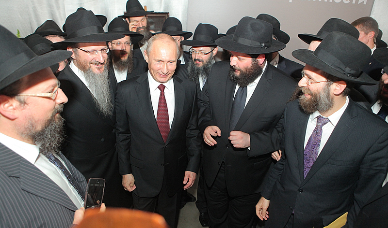 Russia's President Vladimir Putin (C) greets attendees at a ceremony at which the Schneerson library was handed over to the Jewish Museum and Tolerance Center in Moscow on Thursday. Russia's Chief Rabbi Berel Lazar (left of Putin) said the decision to transfer the library to the Jewish Museum and Tolerance Center is a wise one. Lazar promised to do everything possible to ensure that the books will be made accessible to many people. (JDN)