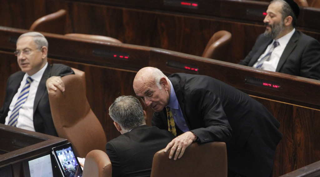 Yesh Atid MK Yaakov Perry leans over to speak with his boss, party chairman and Finance Minister Yair Lapid during a Knesset session, while Prime Minister Binyamin Netanyahu and Shas leader Aryeh Deri sit nearby on Wednesday. (Miriam Alster/FLASH90)