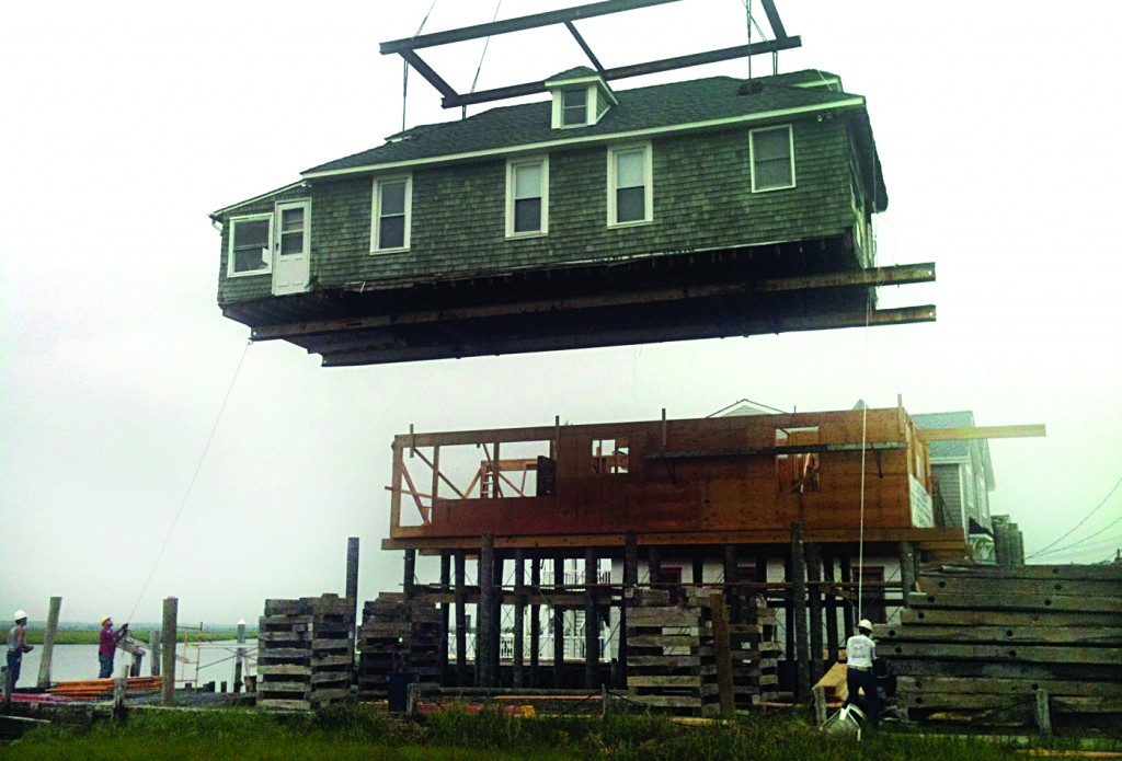 Charlie Lisa's home, a 106-year-old structure in Sea Isle City, N.J., is lifted and moved to the adjoining property to correct damage issues inflicted by Superstorm Sandy. (AP Photo/The Press of Atlantic City, Anjalee Khemlani)