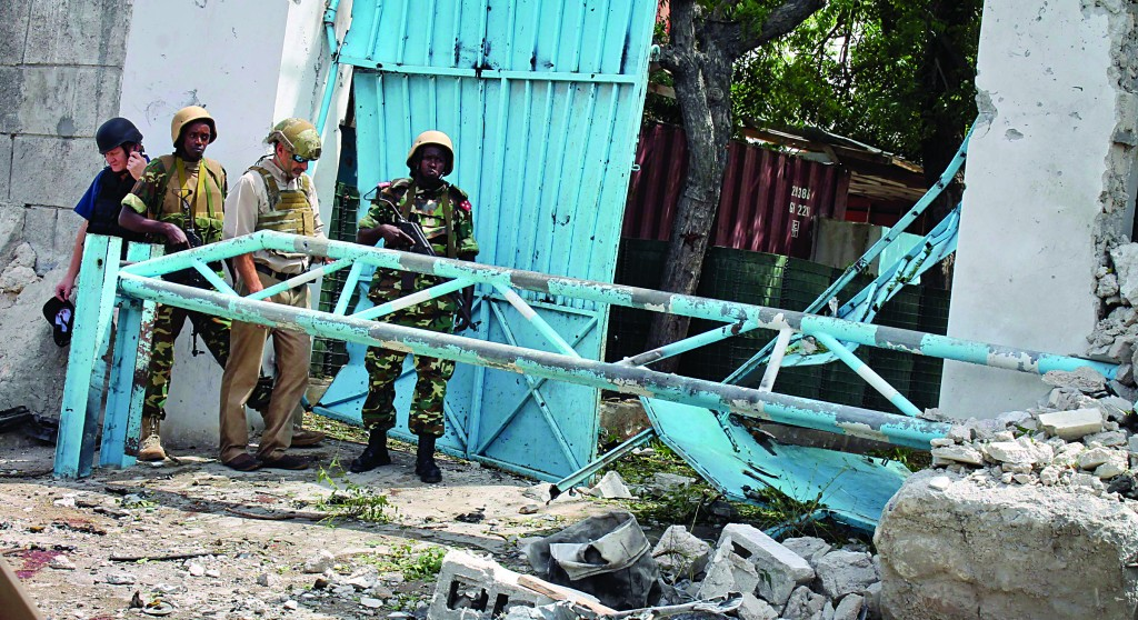 African Union peacekeepers and unidentified foreigners stand outside the main U.N. compound, following an attack on it in Mogadishu, Somalia Wednesday. (AP Photo/Farah Abdi Warsameh)