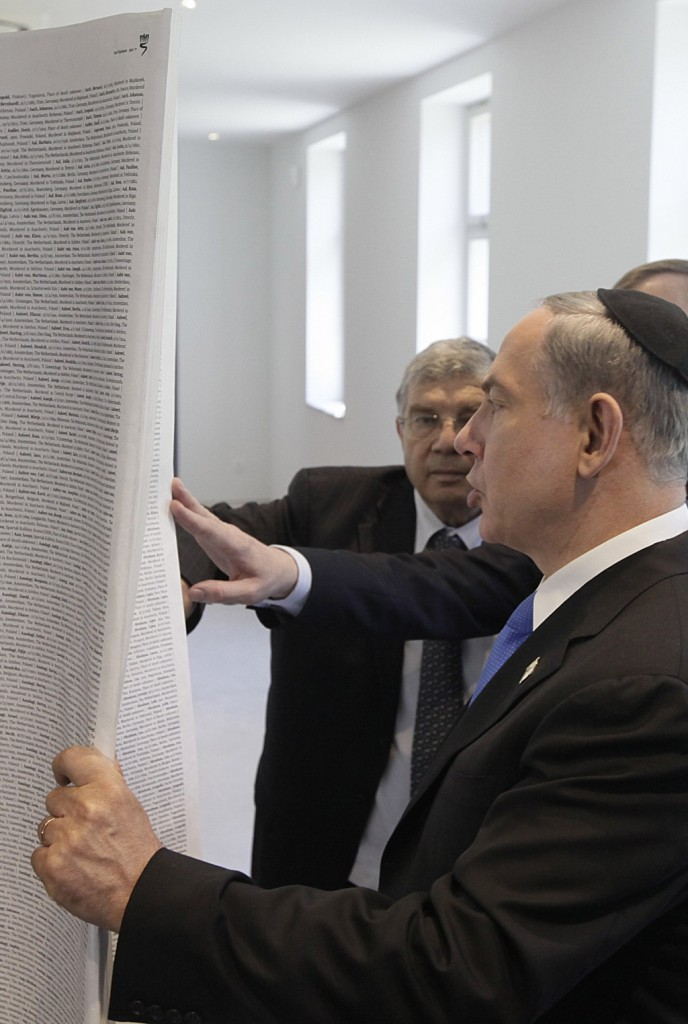 "Israeli Prime Minister Binyamin Netanyahu looks at ""The Book of Names,"" which contains the names of 4.2 million Kedoshim, at the opening of a new pavilion at the former Nazi death camp Auschwitz, in Oswiecim, Poland, on Thursday. Netanyahu made a speech following the opening of the Permanent Exhibition SHOAH at the Auschwitz-Birkenau State Museum, Block 27 in Oswiecim on Thursday. In an apparent reference to the Iranian regime, he said, ""If there are Holocaust deniers, have them come to Block 27 and go over one name at a time."" (AP Photo/Czarek Sokolowski)"