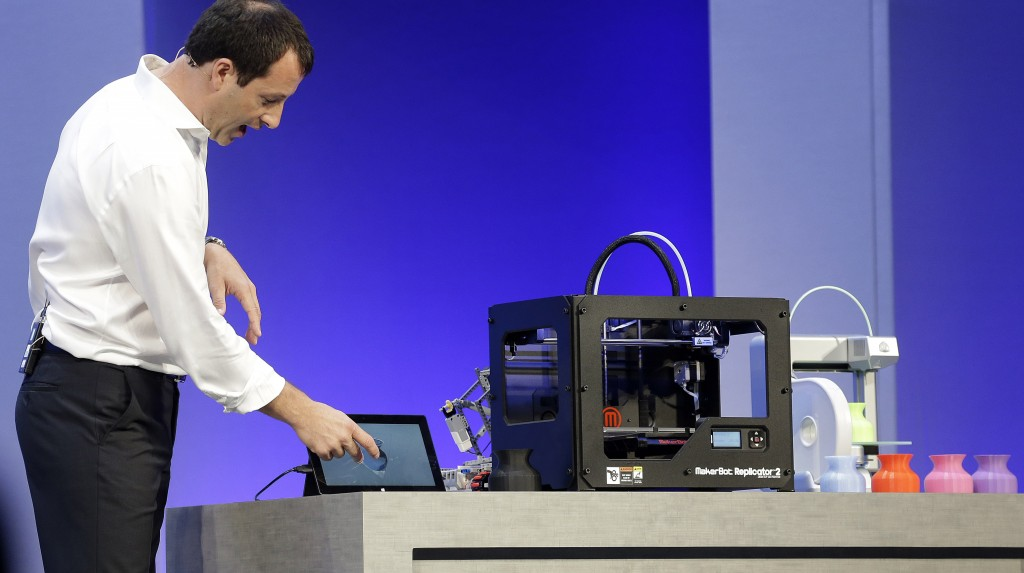 Antoine Leblond, corporate vice president of Windows Program Management, demonstrates printing from a tablet to a 3-D printer while speaking at a Microsoft event in San Francisco Wednesday. (AP Photo/Jeff Chiu)