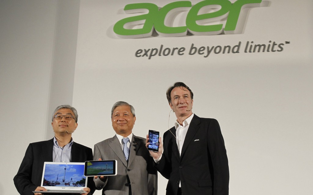 Acer Inc. President Jim Wong (left), Chairman and CEO J.T. Wang (center), and Chief Marketing Officer Michael Birkin stand with their new products at an international press conference on the eve of the opening of Computex, one of the world's largest IT exhibitions, in Taipei, Taiwan on Monday. (AP Photo/Wally Santana)