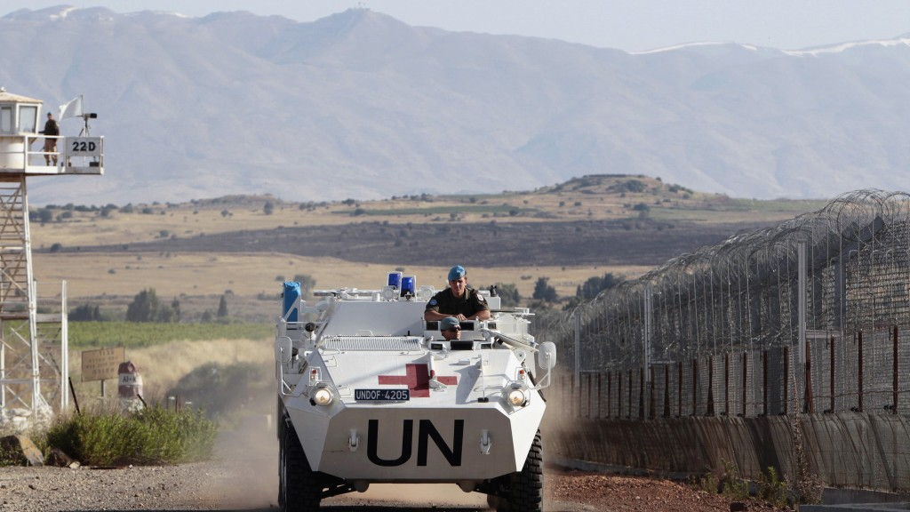 United Nations peacekeeping soldiers from Austria drive past an observation tower near the Quneitra border crossing between Israel and Syria, on the Golan Heights on Wednesday. (REUTERS/Ammar Awad)