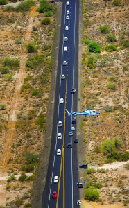 A procession of 19 hearses carrying the bodies of 19 firefighters who died in a wildfire a week ago drives through the desert, Sunday, outside Phoenix. The elite crew of firefighters were overtaken by the out-of-control blaze as they tried to protect themselves from the flames under fire-resistant shields. (AP Photo/Mark J. Terrill)