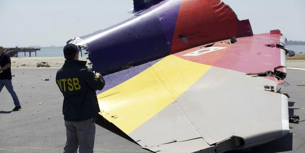 An NTSB agent photographing a part of the Boeing 777 Asiana Airlines Flight 214 aircraft. (AP Photo/NTSB)