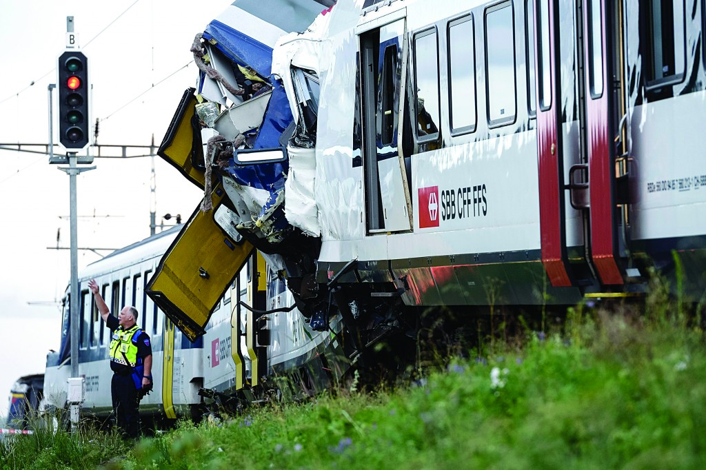 A policeman works at the site where two passenger trains collided head-on in Granges-pres-Marnand, western Switzerland, Monday (AP Photo/Keystone, Laurent Gillieron)