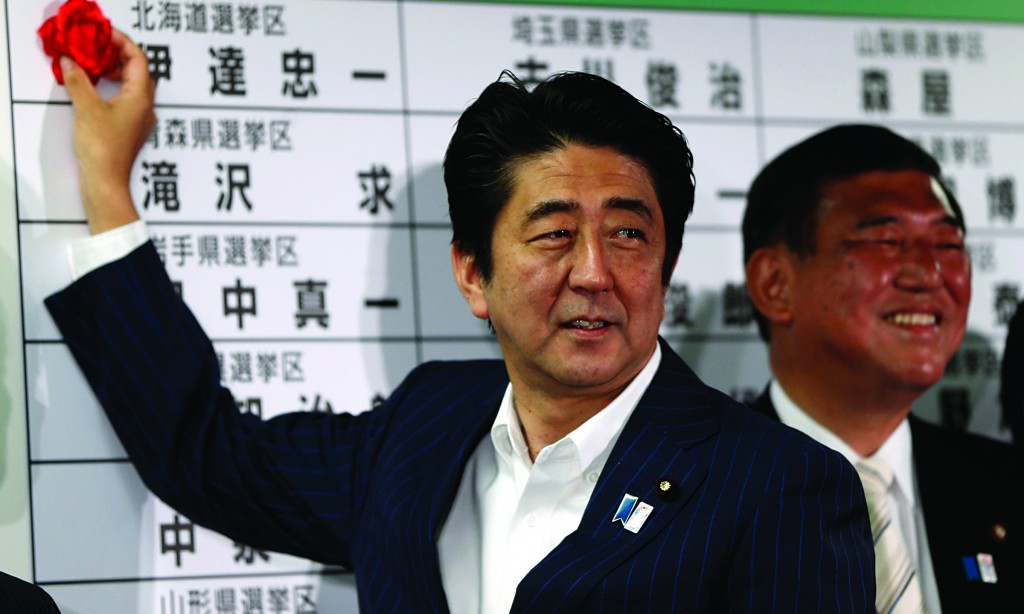 Japan's Prime Minister Shinzo Abe (L), who is also the leader of the ruling Liberal Democratic Party (LDP), puts a rosette on the name of a candidate, next to party Secretary-General Shigeru Ishiba, at the party headquarters in Tokyo, Sunday. (REUTERS/Issei Kato)