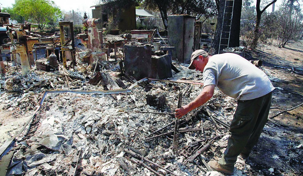 Lon Paul, 53, picks through the remains of his business in Lake Hemet, Calif., after a wildfire passed through the area, Thursday. (AP Photo/Nick Ut)
