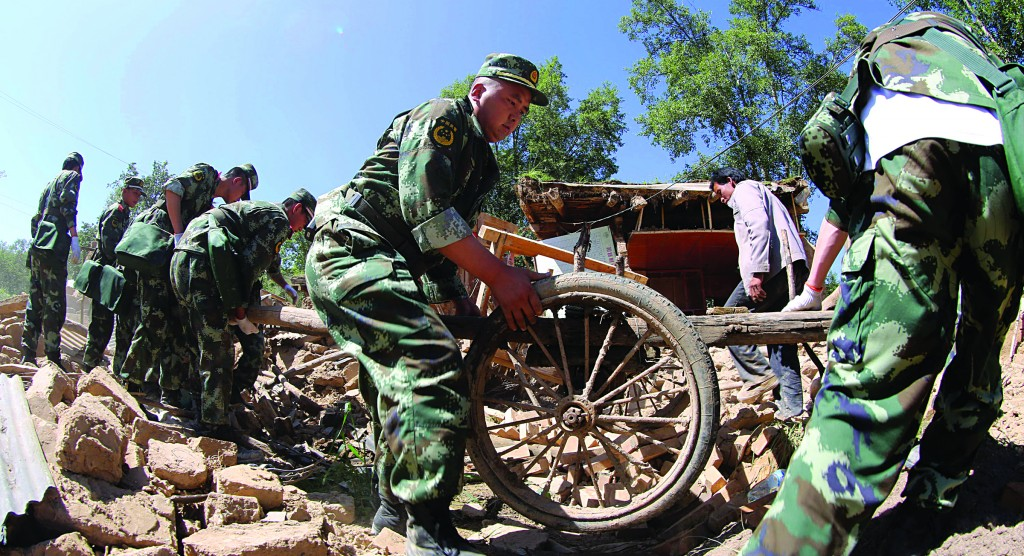 Chinese paramilitary policemen help residents remove belongings from quake damaged houses in northwest China's Gansu province Monday. (AP Photo)