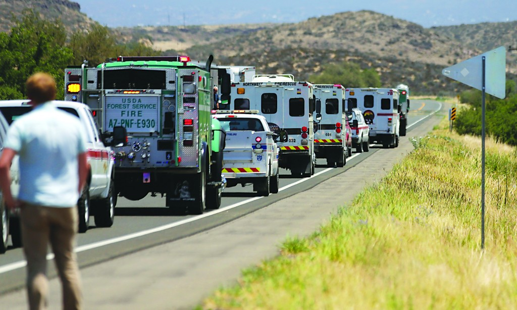 A procession of the vehicles left by the 19 elite Granite Mountain Hotshot crew members killed over the weekend are removed from the fire area near Yarnell, Ariz., Wednesday (AP Photo/Chris Carlson)