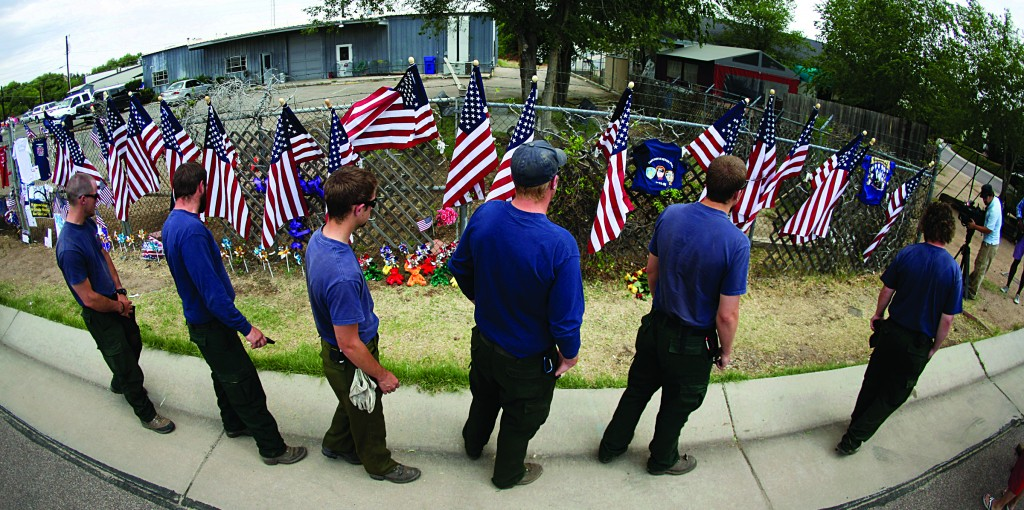 Members of the Centennial Initial Attack Fire Crew, from Island Park, Idaho, pay their respects at a memorial outside the Granite Mountain Interagency Hotshot Crew fire station, Thursday in Prescott, Ariz. (AP Photo/Chris Carlson)
