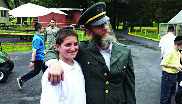 Rabbi Zev Shain, administrator of Camp Karlin Stolin in Highland, N.Y., stands with a camper on Army Day.