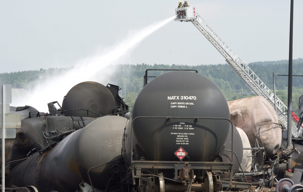 This July 7, 2013 file photo shows firefighters watering railway cars the day after a train derailed causing explosions of railway cars carrying crude oil in Lac Megantic, Que.  (AP Photo/The Canadian Press, Paul Chiasson, File)