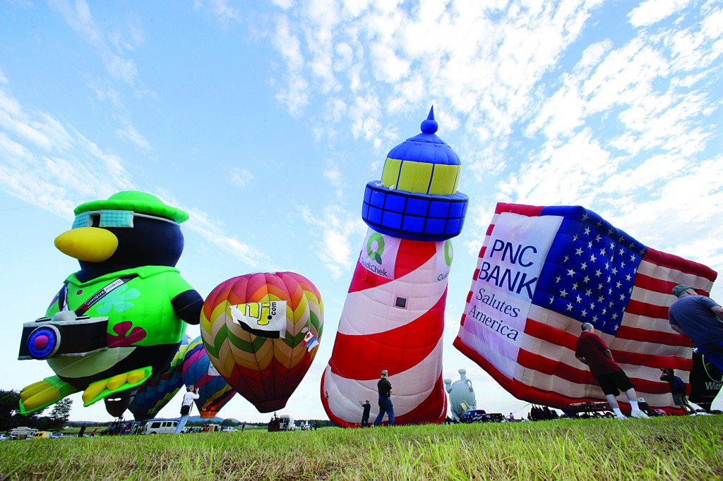 Hot air balloons, including a 115-foot-tall flying lighthouse, are inflated early Friday during the 31st annual QuickChek New Jersey Festival of Ballooning, paying respects to the effort to restore the shore following Superstorm Sandy. (AP Photo/Mel Evans)