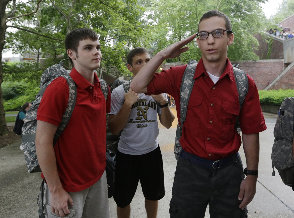 Noah Ogrydziak, right, salutes as he and his brothers Cole, left, and his twin Sumner wait to be processed during Reception Day at West Point Monday.(AP Photo/Mike Groll)