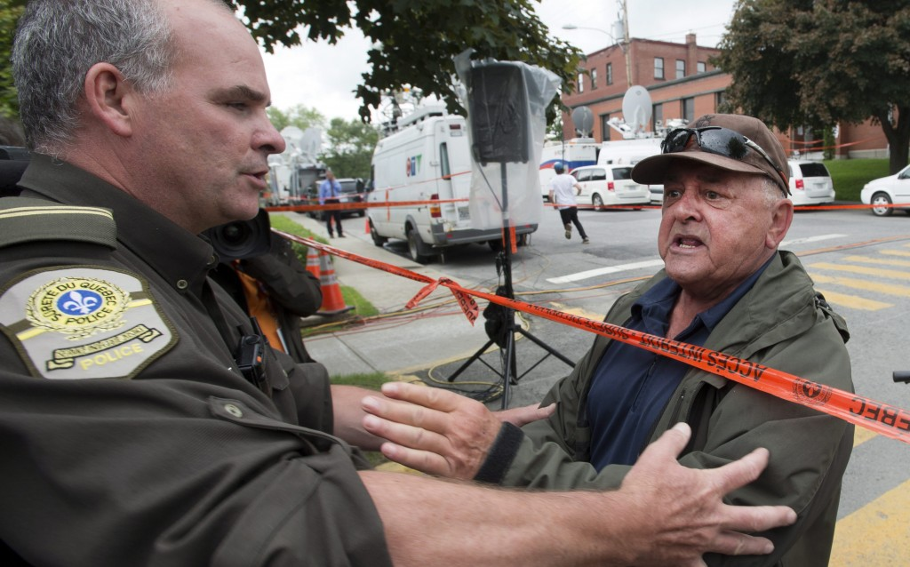 A police officer approaches an angry resident yelling at Ed Burkhardt, president of Rail World Inc., who was speaking in Lac-Megantic, Que., on Wednesday, where a runaway freight train derailed Saturday. All 73 cars were carrying oil; at least five exploded. Canadian officials are telling the families of the 30 people missing that all are presumed dead. With 20 bodies found, that puts the death toll at 50. (AP Photo/The Canadian Press, Ryan Remiorz)