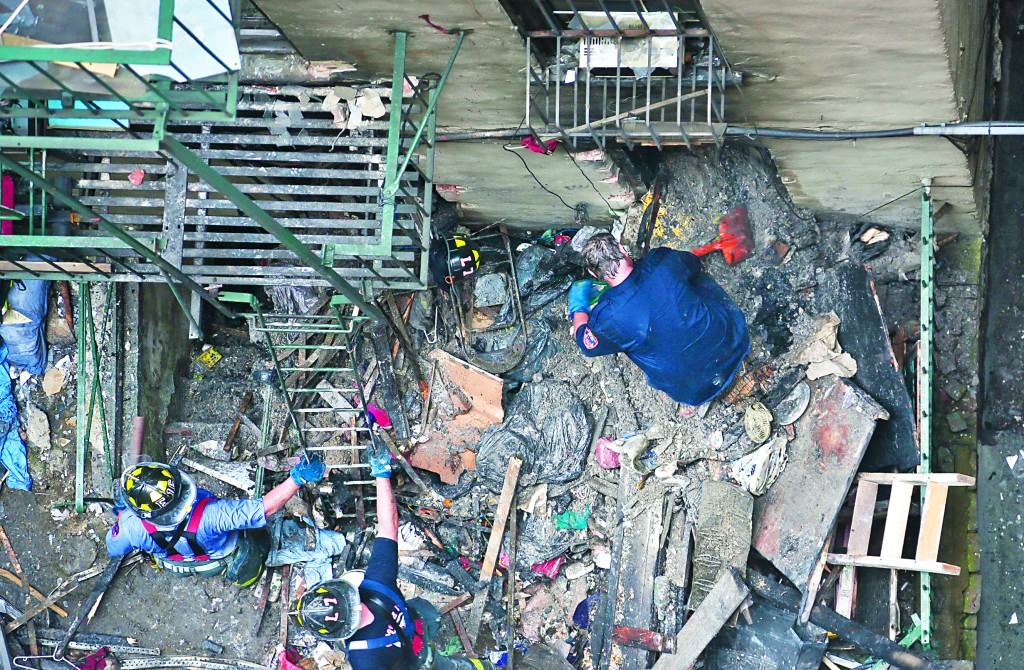In this aerial photo, firefighters remove debris in the aftermath of a fire Thursday in Chinatown.(AP Photo/Bebeto Matthews)