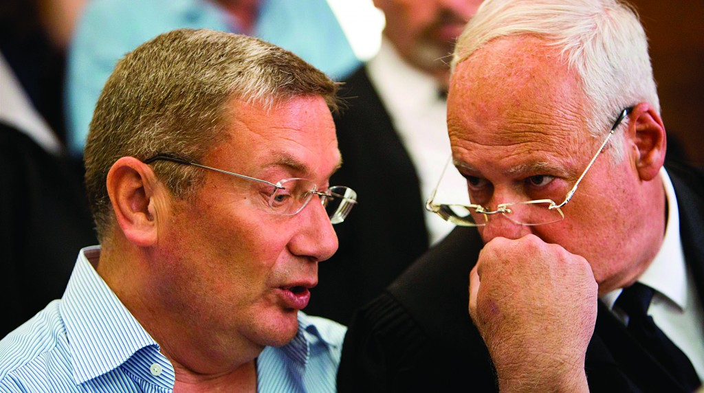 Chairman of IDB Group Nochi Dankner (left) seen talking to his attorney during a recent  session at the Tel Aviv District Court. (Tal Shahar/POOL/Flash90)