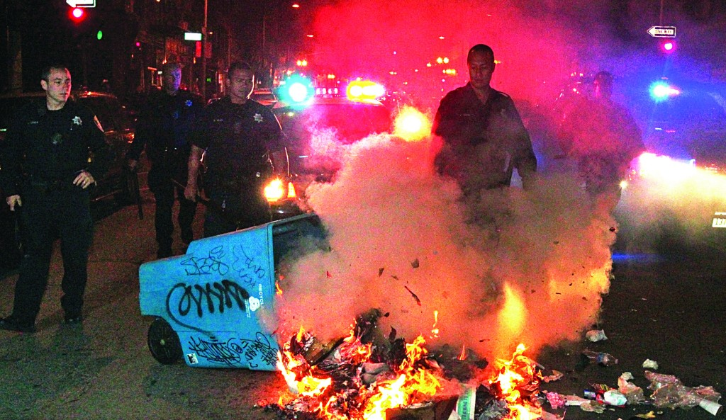 Oakland police officers work to extinguish a fire during a protest after George Zimmerman was found not guilty in the 2012 shooting death of teenager Trayvon Martin, early Sunday in Oakland, Calif. Protesters angered by the acquittal of Zimmerman held largely peaceful demonstrations in three California cities, but broke windows and started small street fires in Oakland, police said. (AP Photo/Bay Area News Group, Anda Chu)