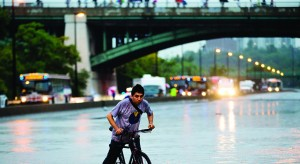 A man rides his bicycle during a flood on the Don Valley Parkway, a major highway, during a heavy rainstorm in Toronto. (REUTERS/Mark Blinch)
