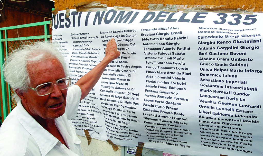Modestino De Angelis, son of Angelo Arturo De Angelis, points the name of his father on the list of victims of the Fosse Ardeatine's massacre, during a demonstration in front of the flat where Nazi war criminal Erich Priebke lives under house arrest, in the day of his 100th birthday, in Rome, Monday.(AP Photo/Riccardo De Luca)