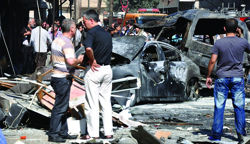 Syrian citizens gather near cars that were burned after a bomb exploded in the suburb of Jaramana, Damascus, Syria. (AP Photo/SANA)
