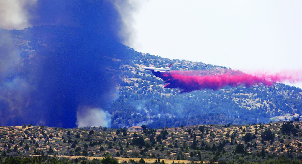 An aerial tanker drops fire retardant on a wildfires threatening homes near Yarnell, Ariz., Monday. (AP Photo/Chris Carlson)