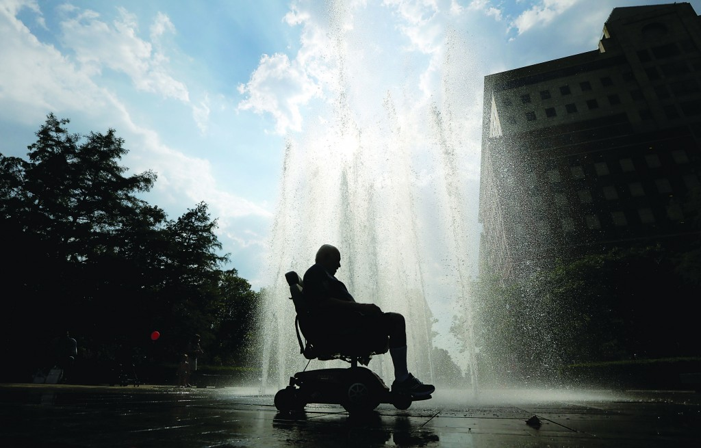 Miguel Torres, 77, rides his electric wheelchair near a fountain Wednesday in Hoboken, N.J. (AP Photo/Julio Cortez)