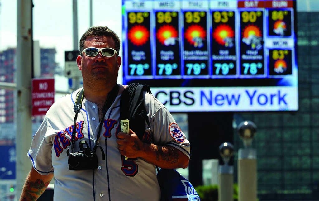 Ricky Otazu, of Lodi, N.J., walks past a giant screen outside the Jacob K. Javits Convention Center announcing the week's weather forecast Tuesday.