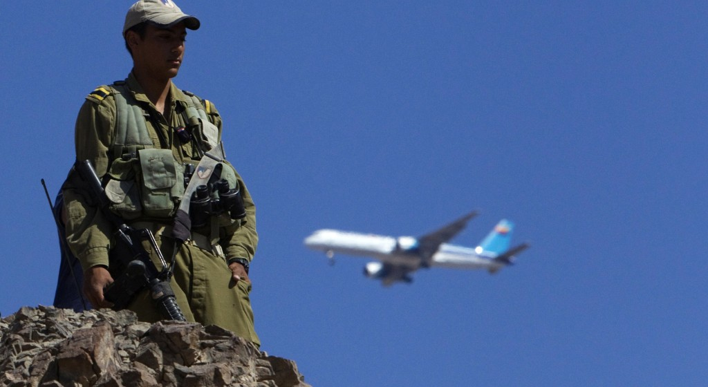 A plane flies overhead as an Israeli soldier stands guard near the Israeli-Egyptian border, close to the Red Sea resort of Eilat. (REUTERS/Ronen Zvulun)