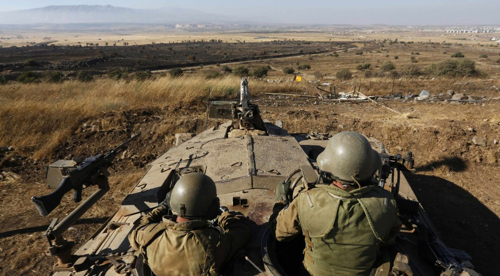Israeli soldiers sit atop a tank as they watch the border with Syria near the Quneitra border crossing between Israel and Syria, on the Golan Heights. (REUTERS/Baz Ratner)