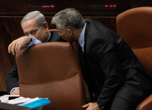 Finance Minister Yair Lapid (R) conferring with Prime Minister Binyamin Netanyahu during the budget debate in the Knesset on Monday. (Miriam Alster/FLASH90)
