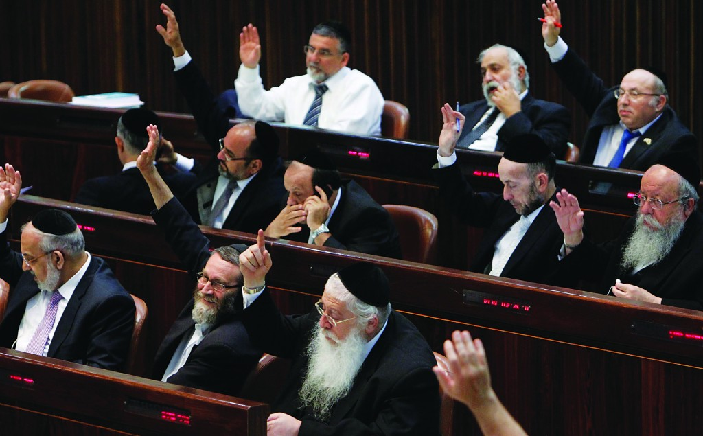 Voting by hand on the budget in the Knesset on Monday. (Miriam Alster/FLASH90)